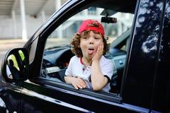 Το παιδί με τη σγουρή τρίχα και μια κόκκινη ΚΑΠ κάθεται πίσω από τη ρόδα του αυτοκινήτου Στοκ εικόνα με δικαίωμα ελεύθερης χρήσης