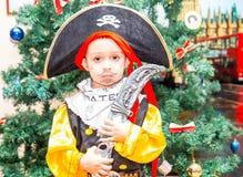 Το παιδί μικρών παιδιών έντυσε ως πειρατής για αποκριές στο υπόβαθρο του χριστουγεννιάτικου δέντρου Στοκ Εικόνα