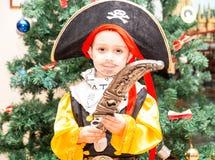 Το παιδί μικρών παιδιών έντυσε ως πειρατής για αποκριές στο υπόβαθρο του χριστουγεννιάτικου δέντρου Στοκ Εικόνες
