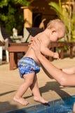 Το παιδί μικρών παιδιών πηγαίνει στα χέρια του πατέρα του στη λίμνη Στοκ Εικόνα