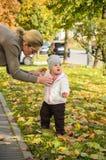 Το παιδί μωρών έχει τη διασκέδαση με τα φύλλα φθινοπώρου Στοκ Εικόνες