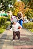 Το παιδί μωρών έχει τη διασκέδαση με τα φύλλα φθινοπώρου Στοκ Φωτογραφία