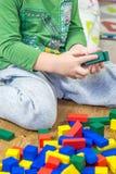 Το παιδί παίζει με τους πολύχρωμους κύβους στο ξύλινο πάτωμα Στοκ Εικόνες
