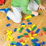 Το παιδί παίζει με τους πολύχρωμους κύβους στο ξύλινο πάτωμα Στοκ Εικόνα