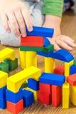 Το παιδί παίζει με τους πολύχρωμους κύβους στο ξύλινο πάτωμα Στοκ εικόνες με δικαίωμα ελεύθερης χρήσης