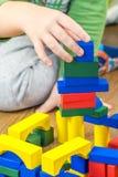 Το παιδί παίζει με τους πολύχρωμους κύβους στο ξύλινο πάτωμα Στοκ φωτογραφία με δικαίωμα ελεύθερης χρήσης