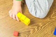 Το παιδί παίζει με τους πολύχρωμους κύβους στο ξύλινο πάτωμα Στοκ φωτογραφίες με δικαίωμα ελεύθερης χρήσης
