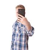Το παιδί παίρνει μια φωτογραφία με το τηλέφωνό του που απομονώνεται στο λευκό Στοκ φωτογραφίες με δικαίωμα ελεύθερης χρήσης