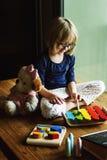 Το παιδί που παίζει το παιχνίδι Xylophone απολαμβάνει την έννοια στοκ φωτογραφία