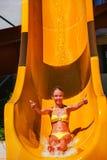 Το παιδί στη φωτογραφική διαφάνεια νερού στο aquapark παρουσιάζει αντίχειρες Στοκ Φωτογραφία