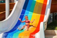 Το παιδί στο aquapark γλιστρά κάτω από τη φωτογραφική διαφάνεια νερού Στοκ Φωτογραφία
