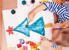 Το παιδί σύρει μια βούρτσα και τα χρώματα Στοκ Εικόνα