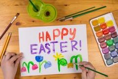 Το παιδί σύρει τη ευχετήρια κάρτα για ευτυχές Πάσχα Στοκ φωτογραφία με δικαίωμα ελεύθερης χρήσης
