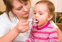 το παιδί ταΐζει mums Στοκ Φωτογραφία