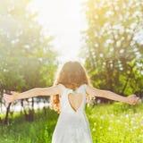 Το παιδί τα όπλα απολαμβάνοντας το καθαρό αέρα και το φως του ήλιου Στοκ Φωτογραφία