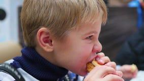 Το παιδί τρώει ένα scone με το κοτόπουλο στο εστιατόριο γρήγορου φαγητού απόθεμα βίντεο
