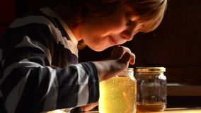 Το παιδί τρώει το μέλι απόθεμα βίντεο