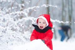 Το παιδί χτίζει έναν χιονάνθρωπο από το χιόνι Στοκ εικόνες με δικαίωμα ελεύθερης χρήσης