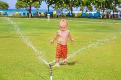 Το παιδικό παιχνίδι, κολυμπά και καταβρέχει κάτω από τον ψεκασμό ψεκαστήρων νερού Στοκ Φωτογραφίες