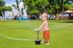 Το παιδικό παιχνίδι, κολυμπά και καταβρέχει κάτω από τον ψεκασμό ψεκαστήρων νερού Στοκ φωτογραφία με δικαίωμα ελεύθερης χρήσης