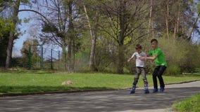 Το παλαιότερο αγόρι βοηθά το μικρότερο αδερφό του για να μάθει να οδηγά στα σαλάχια κυλίνδρων απόθεμα βίντεο