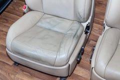 Το παλαιό βρώμικο μπεζ χρώμα καθισμάτων αυτοκινήτων του διατρυπημένου δέρματος με τις ρωγμές και γρατζουνίζει στο εργαστήριο για  στοκ εικόνα με δικαίωμα ελεύθερης χρήσης