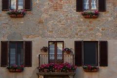 Το παλαιό μπαλκόνι της Τοσκάνης με το γεράνι ανθίζει στο μικρό μαγικό και παλαιό χωριό Pienza, Val Δ ` Orcia Τοσκάνη †«Ιταλία Στοκ φωτογραφία με δικαίωμα ελεύθερης χρήσης