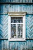 Το παλαιό ξεπερασμένο ξύλινο παράθυρο με τις αρθρώσεις και τα χαρασμένα παραθυρόφυλλα αναδρομικός στοκ φωτογραφία