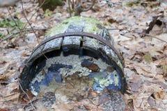 Το παλαιό ξύλινο βαρέλι με τα πλαίσια σιδήρου, που σπάζουν και σάπια, βρίσκεται στο δάσος φθινοπώρου στα ξηρά φύλλα Στοκ Εικόνα