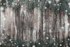 Το παλαιό ξύλινο υπόβαθρο με το διάστημα για τη ευχετήρια κάρτα με το πράσινο έλατο διακλαδίζεται στην κορυφή και το κατώτατο σημ Στοκ Εικόνες
