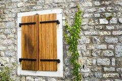 Το παλαιό παράθυρο με τα κλειστά παραθυρόφυλλα στο παλαιό σπίτι Ο κισσός εισάγει τον τοίχο πετρών Στοιχείο της πρόσοψης του παλαι Στοκ Εικόνες