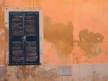 Το παλαιό παράθυρο με τα πράσινα χρωματισμένα κλειστά ξύλινα παραθυρόφυλλα σε ένα πορτοκαλί μεσογειακό ocher χρωμάτισε την πορτοκ στοκ φωτογραφίες με δικαίωμα ελεύθερης χρήσης
