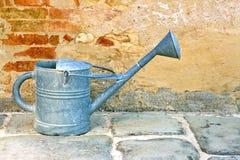 Το παλαιό πότισμα μπορεί από ένα αγροτικό brickwall Στοκ εικόνα με δικαίωμα ελεύθερης χρήσης