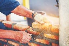 Το παλαιό χέρι ατόμων ασπρίζει χτισμένο το τσιμέντο καινούργιο σπίτι τούβλου τοίχων, τούβλο Στοκ Φωτογραφίες