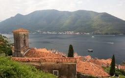 Το παλαιό χωριό στην ακτή του κόλπου Πορτοκαλιά στέγη στο πρώτο πλάνο στοκ εικόνες