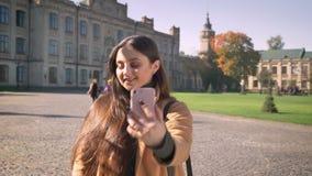 Το πανέμορφο καυκάσιο θηλυκό παίρνει selfies στο τηλέφωνό της στεμένος υπαίθριος, την αποκατάσταση της τρίχας της και το χαμόγελο απόθεμα βίντεο