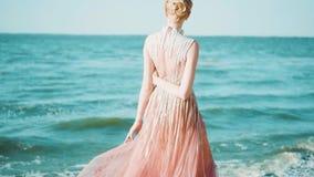 Το πανέμορφο κορίτσι στο μακρύ ανοικτό ροζ λαμπρό φόρεμα που αφήνεται μόνο στο νησί, κοντά στο μεγάλο μπλε ωκεανό, κρατά το χέρι  απόθεμα βίντεο