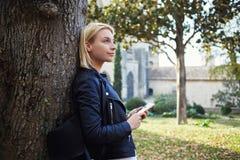 Το πανέμορφο νέο κορίτσι hipster κρατά το τηλέφωνο κυττάρων και ονειρεύεται για κάτι Στοκ εικόνες με δικαίωμα ελεύθερης χρήσης