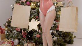 Το πανέμορφο νέο πρότυπο στέκεται με παρουσιάζει κοντά στο χριστουγεννιάτικο δέντρο στο εσωτερικό φιλμ μικρού μήκους