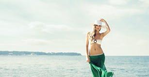 Το πανέμορφο, προκλητικό κορίτσι που φορούν το καπέλο, το μπικίνι και το πράσινο μετάξι είναι Στοκ φωτογραφία με δικαίωμα ελεύθερης χρήσης