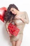 Το πανέμορφο προκλητικό σγουρό brunette τρίχας στην εκμετάλλευση φορεμάτων τύλιξε το κόκκινα δώρο και το μπαλόνι Στοκ φωτογραφία με δικαίωμα ελεύθερης χρήσης