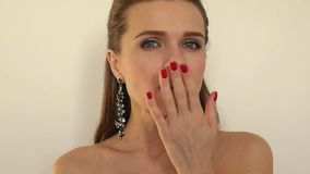 Το πανέμορφο όμορφο κορίτσι με τα μακριά σκουλαρίκια κάνει ένα φιλί προς τη κάμερα σε ένα άσπρο υπόβαθρο, 1920x1080, απόθεμα βίντεο