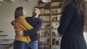 Το παντρεμένο ζευγάρι αγοράζει το διαμέρισμα, τινάζοντας τα χέρια με το θηλυκό κτηματομεσίτη φιλώντας και που γελά έπειτα που αγκ απόθεμα βίντεο