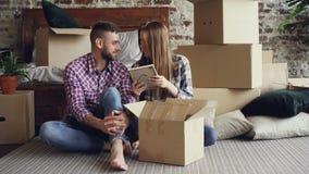 Το παντρεμένο ζευγάρι ανοίγει τα προσωπικά πράγματα καθμένος στο πάτωμα στο καινούργιο σπίτι Οι νέοι μιλούν και γελούν απόθεμα βίντεο