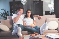 Το παντρεμένο ζευγάρι είναι διασκεδαστικό με τον ενδιαφέροντα κινηματογράφο στο σπίτι στοκ φωτογραφίες