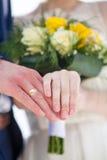 Το παντρεμένο ζευγάρι κρατά τα χέρια τους με τα γαμήλια δαχτυλίδια Στοκ Εικόνες