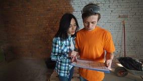 Το παντρεμένο ζευγάρι στο ελλιπές δωμάτιο κοιτάζει στο σχέδιο του μελλοντικού σπιτιού και αγκαλιάζει απόθεμα βίντεο