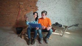 Το παντρεμένο ζευγάρι στο ελλιπές δωμάτιο κοιτάζει στο σχέδιο του μελλοντικού σπιτιού και αγκαλιάζει φιλμ μικρού μήκους