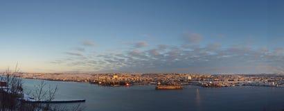 Το πανόραμα της πόλης θάλασσας στο ηλιοβασίλεμα, η παλαιά αποβάθρα σκαφών στέκεται στην αποβάθρα στη μέση του κόλπου Στοκ Εικόνα