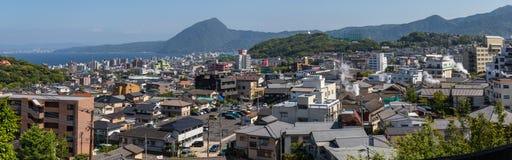 Το πανόραμα του ορίζοντα της πόλης και του κόλπου Beppu, με τον καυτό ατμό στοκ εικόνα